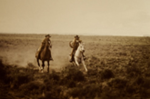 two cowboys on horseback galloping